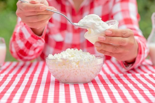 Menina com camisa xadrez vermelha colher creme azedo em queijo cottage com colher