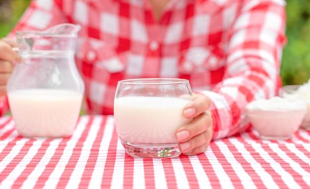 Menina com camisa xadrez vermelha segurando um copo de leite fresco