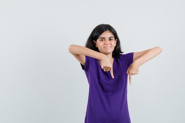Menina com camiseta apontando para baixo e parecendo feliz,