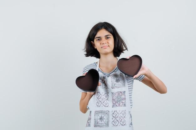 Menina com camiseta, avental segurando uma caixa de presente vazia,