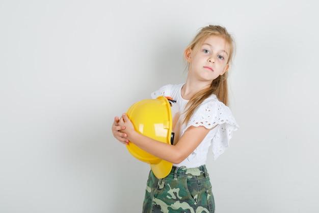 Menina com camiseta branca, saia abraçando o capacete de segurança e parecendo confiante