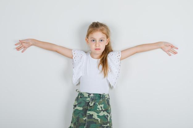 Menina com camiseta branca, saia abrindo os braços e parecendo enérgica