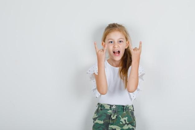 Menina com camiseta branca, saia com cartaz de rock and roll