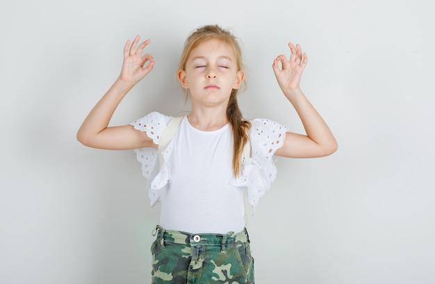 Menina com camiseta branca, saia meditando com os olhos fechados