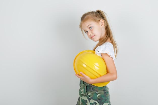 Menina com camiseta branca, saia segurando capacete de segurança e olhando para longe