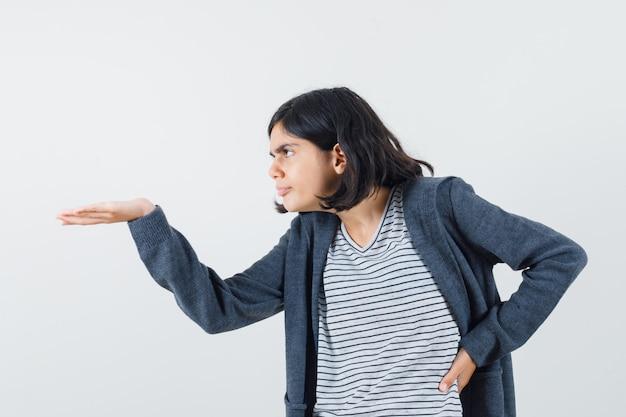 Menina com camiseta e jaqueta esticando a mão de maneira questionadora e intrigada