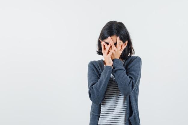 Menina com camiseta e jaqueta olhando por entre os dedos e parecendo curiosa