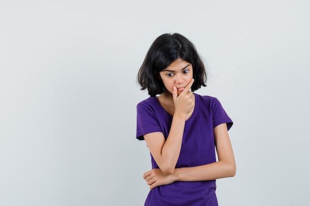 Menina com camiseta em pé, pensando e parecendo surpresa,