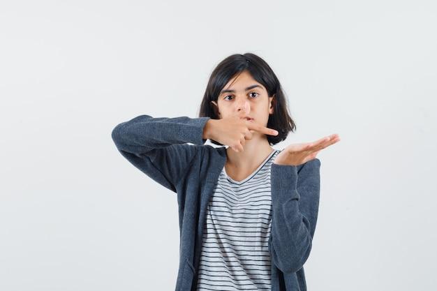Menina com camiseta, jaqueta apontando para a palma da mão aberta para o lado e parecendo confusa