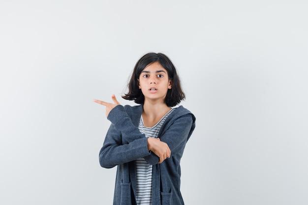 Menina com camiseta, jaqueta apontando para o lado e parecendo confusa