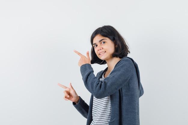 Menina com camiseta, jaqueta apontando para o lado e parecendo curiosa