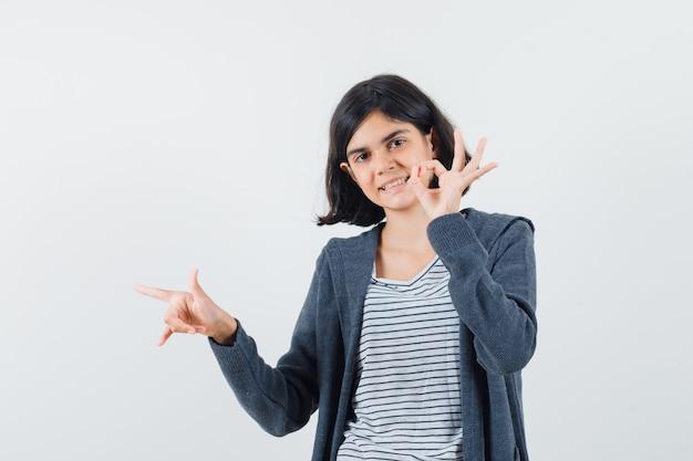 Menina com camiseta, jaqueta apontando para o lado, mostrando sinal de ok e parecendo feliz