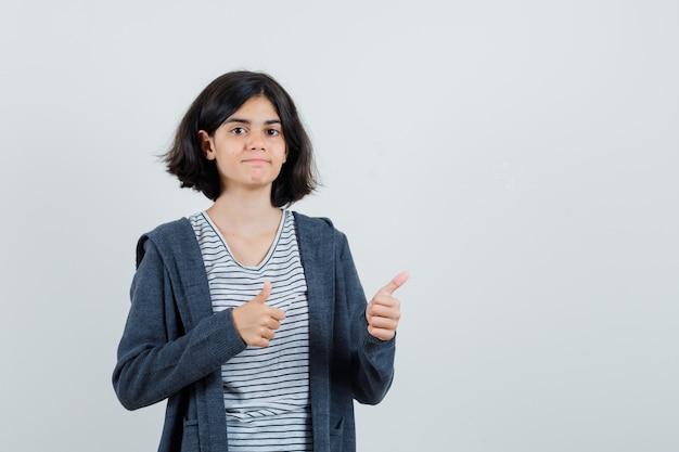 Menina com camiseta, jaqueta com dois polegares para cima e parecendo confiante,