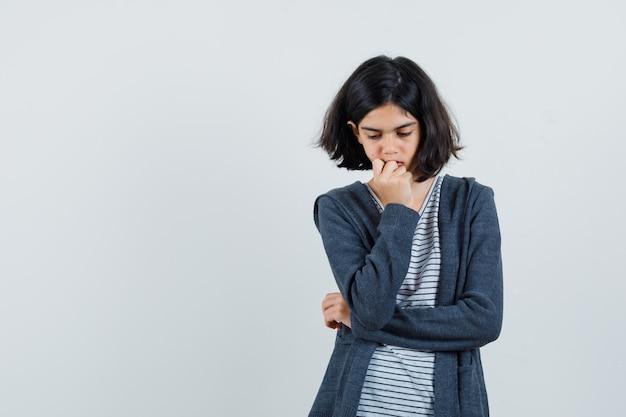 Menina com camiseta, jaqueta, em pose pensativa e parecendo triste,