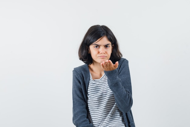 Menina com camiseta, jaqueta esticando a mão em um gesto de questionamento e parecendo confusa