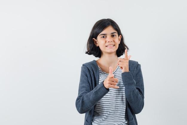Menina com camiseta, jaqueta mostrando o gesto da arma e parecendo confiante