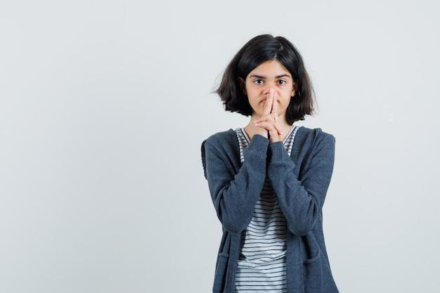 Menina com camiseta, jaqueta mostrando o gesto da arma e parecendo esperançosa,