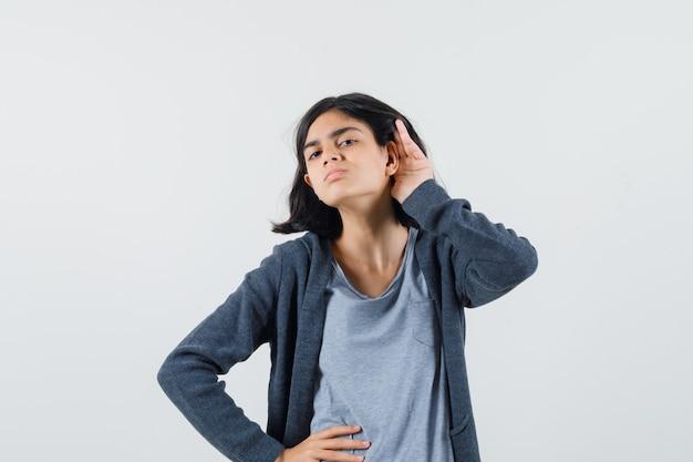 Menina com camiseta, jaqueta segurando a mão atrás da orelha e parecendo curiosa