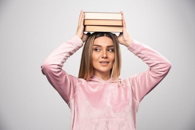 Menina com camiseta rosa segurando os livros sobre a cabeça