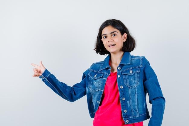 Menina com camiseta vermelha e jaqueta jeans apontando para a esquerda com o dedo indicador e parecendo feliz