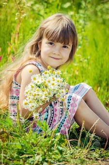 Menina com camomila. foco seletivo. flores da natureza.
