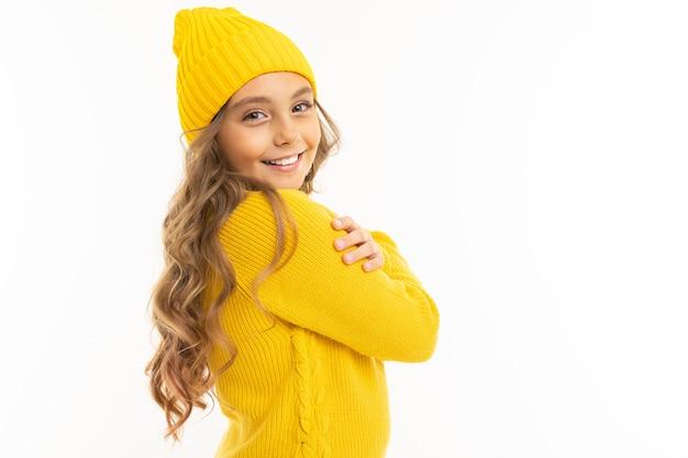 Menina com capuz amarelo e chapéu desfrutando, retrato isolado no branco