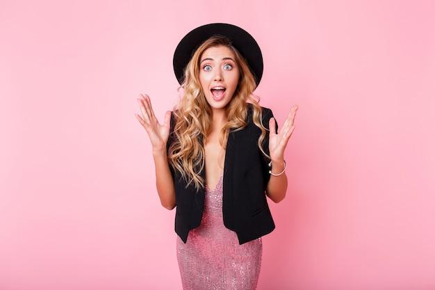 Menina com cara de surpresa em cima de parede rosa. usando vestido elegante com lantejoulas. emoções espantadas. vestido da moda com sequência, jaqueta preta e chapéu.