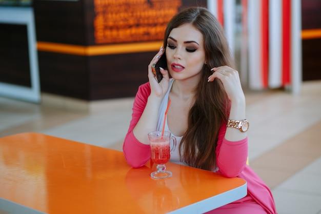 Menina com cara séria fala no telefone sentado em um restaurante