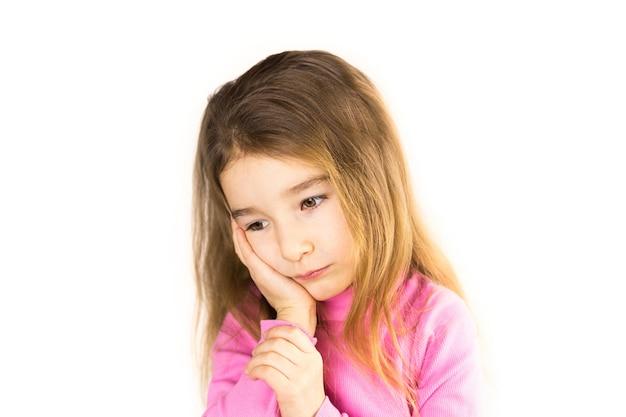Menina com cara triste segura sua bochecha com a mão - o dente dói. dor de ouvido