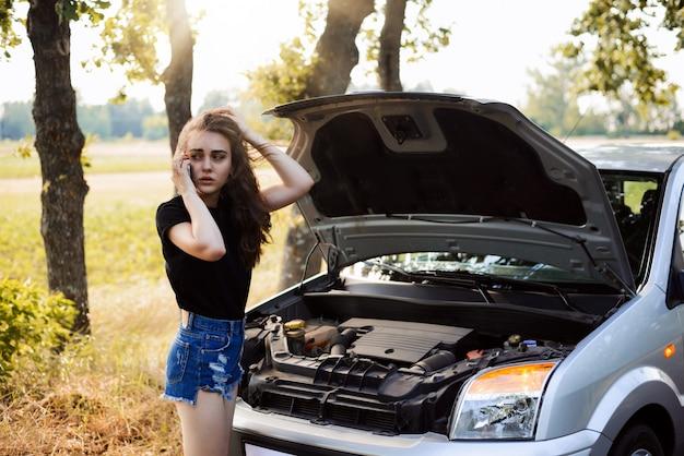 Menina com carro quebrado na esquina para chamar alguém para uma ajuda