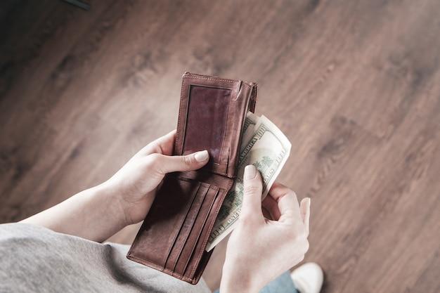Menina com carteira nas mãos e pega dinheiro