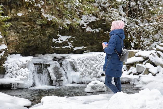 Menina com casaco azul em pé com uma caneca