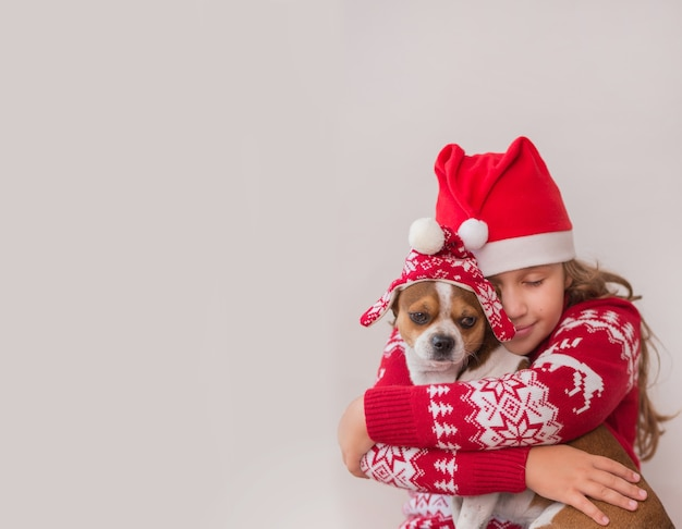 Menina com casaco de natal e chapéu segurando cachorrinho com chapéu de inverno