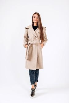 Menina com casaco de outono em um fundo branco