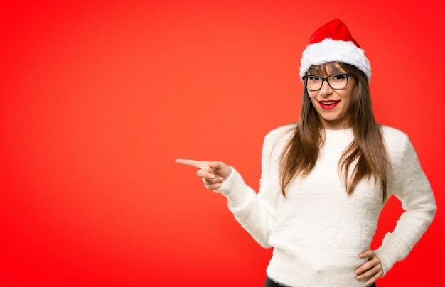 Menina, com, celebrando, a, natal, feriados, apontar dedo, para, a, lado, e, apresentando, um