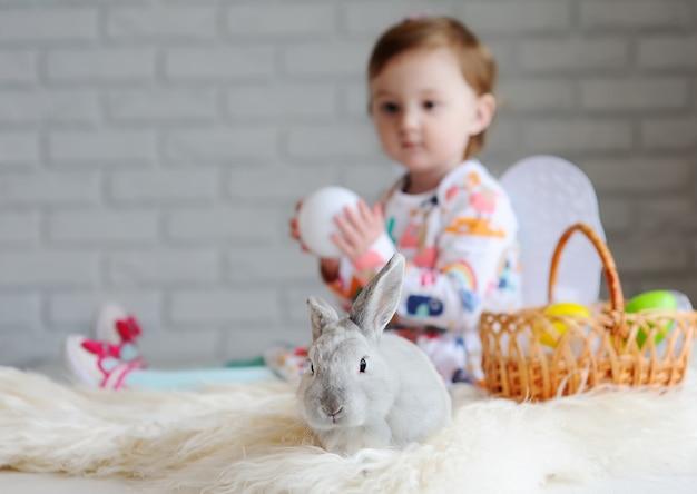 Menina com cesta de páscoa e coelhinho da páscoa