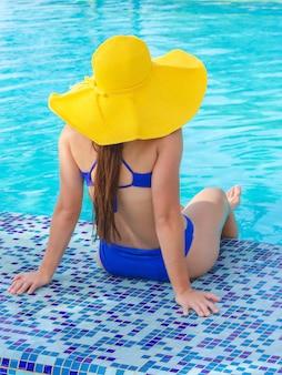 Menina com chapéu amarelo na piscina azul