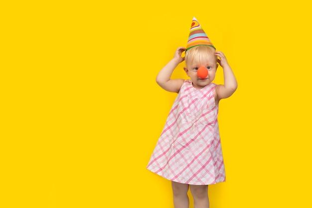 Menina com chapéu de festa e nariz de palhaço vermelho sobre amarelo