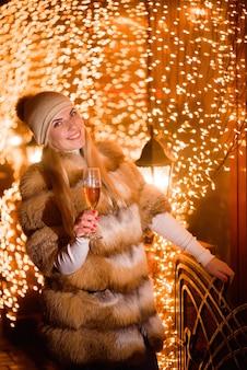Menina com chapéu de inverno elegante com taça de champanhe na festa sobre fundo dourado brilhante de férias.