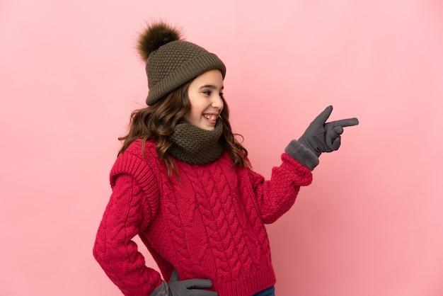 Menina com chapéu de inverno isolada em fundo rosa apontando o dedo para o lado e apresentando um produto