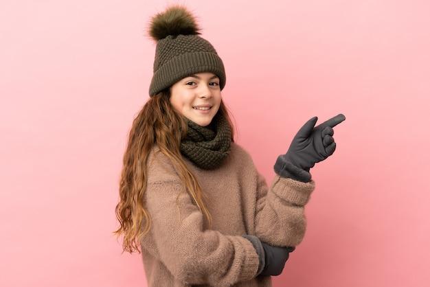 Menina com chapéu de inverno isolada em fundo rosa apontando o dedo para o lado