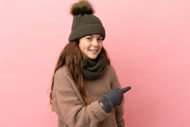 Menina com chapéu de inverno isolada em fundo rosa apontando para trás