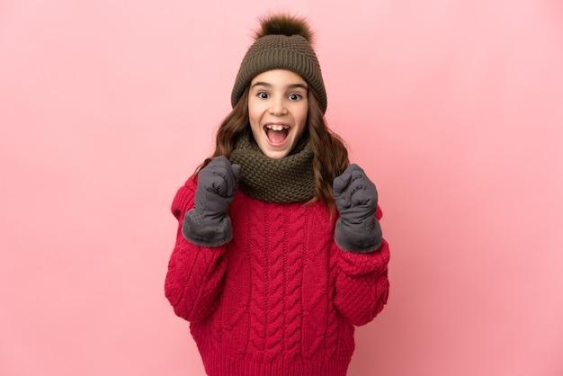 Menina com chapéu de inverno isolada em fundo rosa comemorando vitória na posição de vencedora