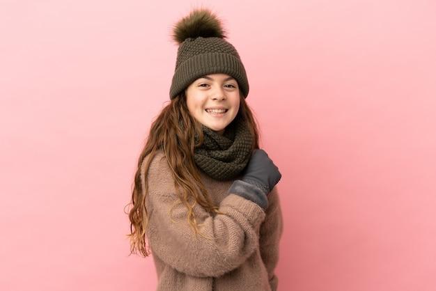 Menina com chapéu de inverno isolada em fundo rosa comemorando vitória