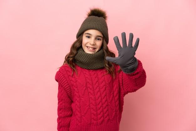 Menina com chapéu de inverno isolada em fundo rosa contando cinco com os dedos