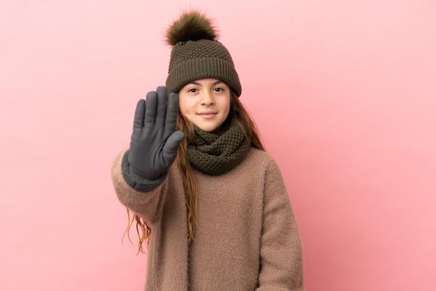 Menina com chapéu de inverno isolada em fundo rosa fazendo gesto de pare