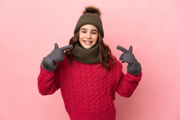 Menina com chapéu de inverno isolada em fundo rosa fazendo gesto de polegar para cima