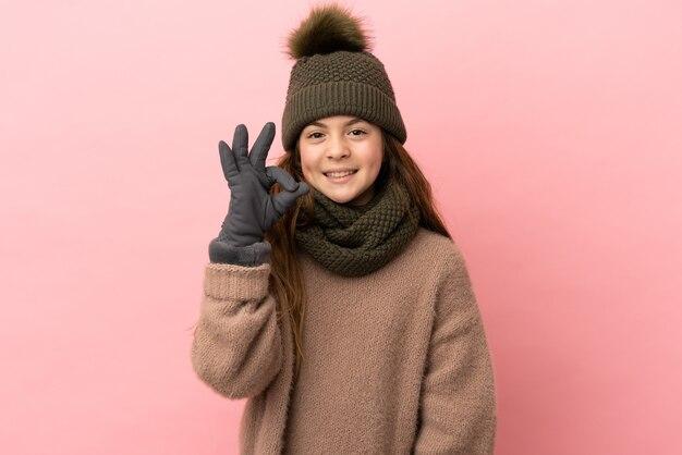 Menina com chapéu de inverno isolada em fundo rosa mostrando sinal de ok com os dedos