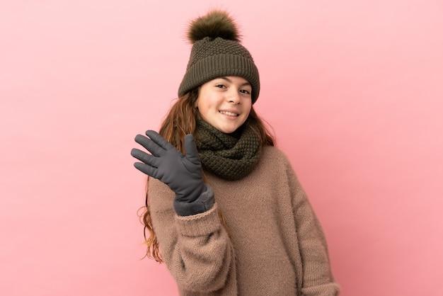 Menina com chapéu de inverno isolada em fundo rosa saudando com a mão com expressão feliz