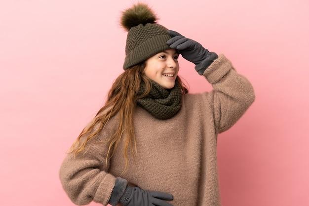 Menina com chapéu de inverno isolada em fundo rosa sorrindo muito